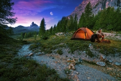 Mystical night landscape, in the foreground hike, campfire and tent